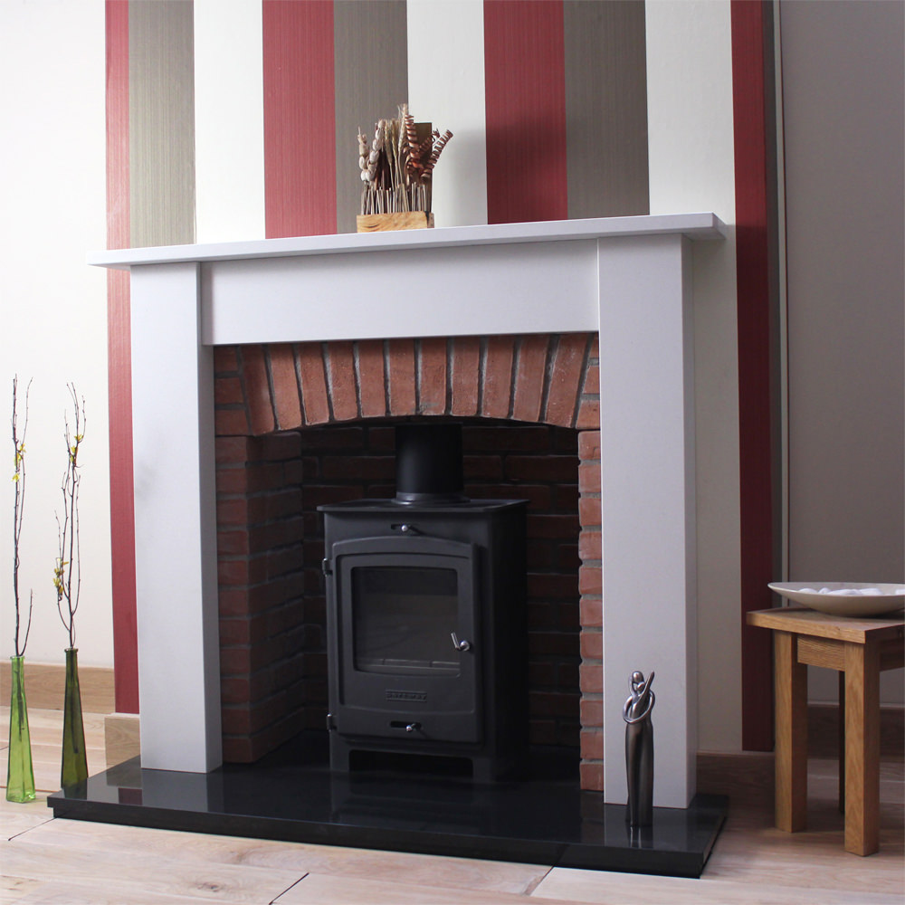 Oxford marble fireplace shown in a Spanish Blanco Micro marble shown with a stove and brick chamber